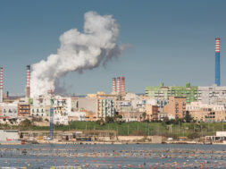 White smoke going up from the chimney of steel plant of  Taranto, Puglia. Italy